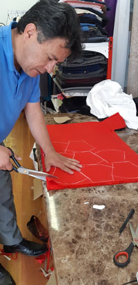 A man holding scissors to a piece of red material with mask shapes drawn on it.